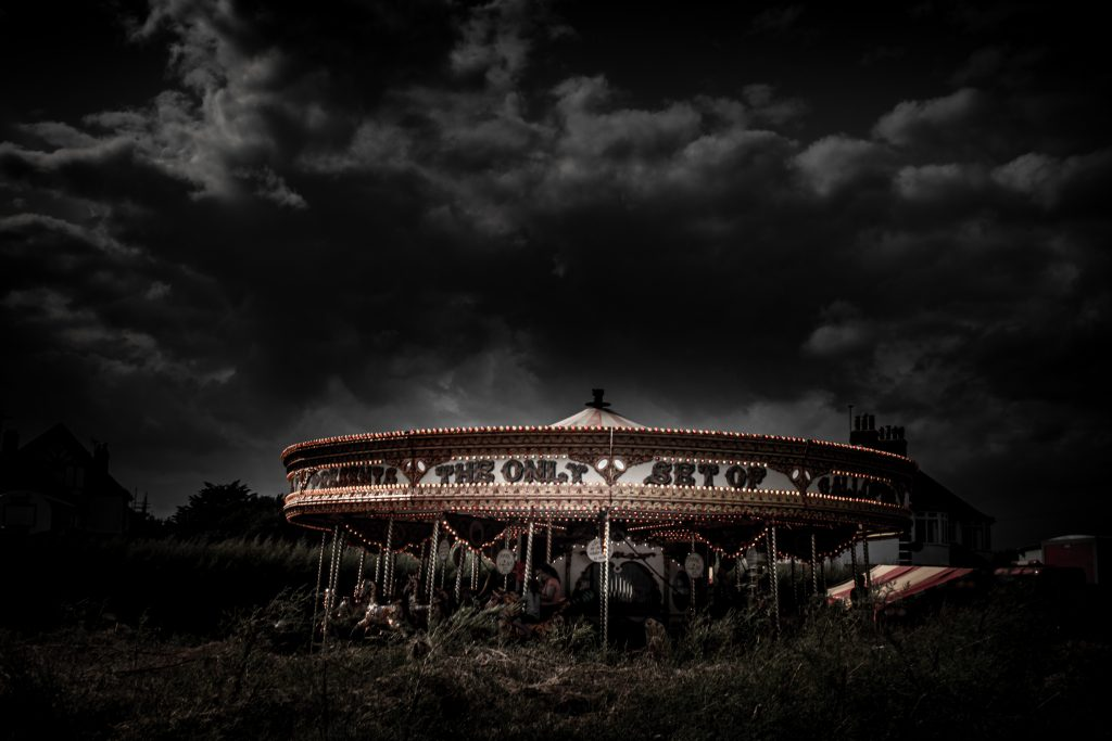 Digital print of a merry-go-round at night with a dark sky