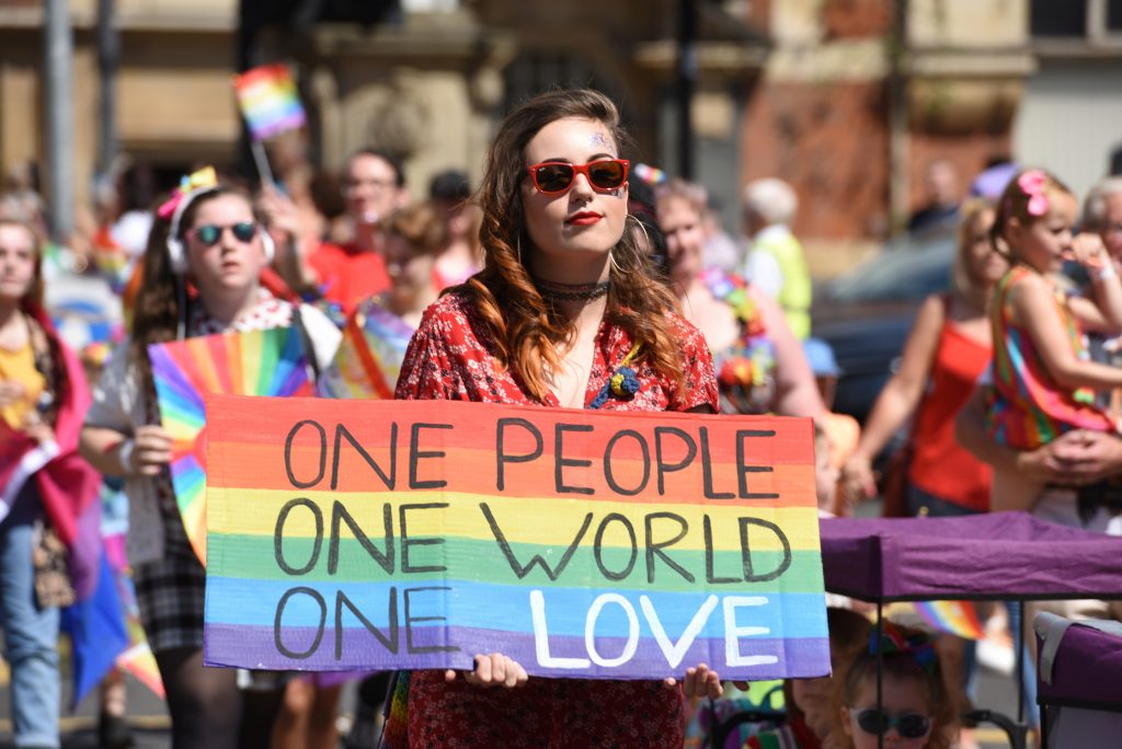 A photo of people celebrating Pride in Hull. In the foreground a young woman holds a rainbow banner with the words one people, one world, one love written on it.