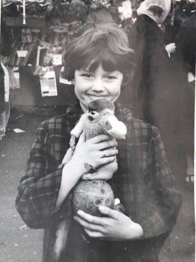 A girl smiles as she holds a monkey