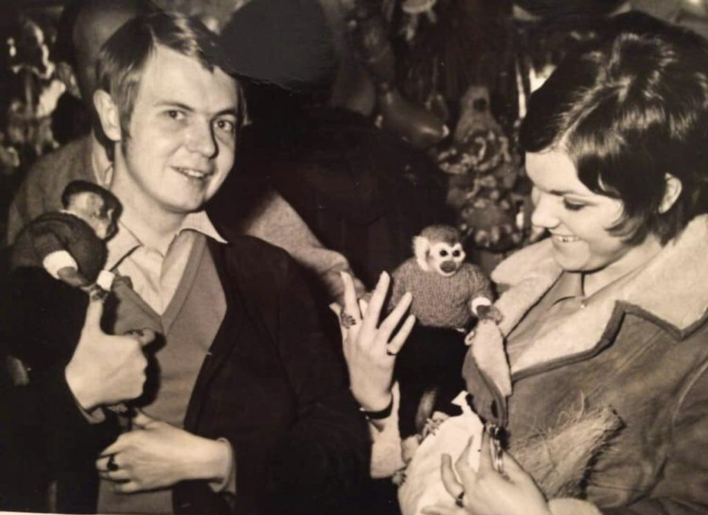 A man and a women hold monkeys at the fair