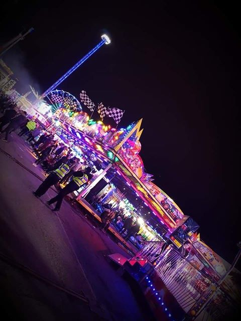 A colour photograph showing police walking around the fair at night