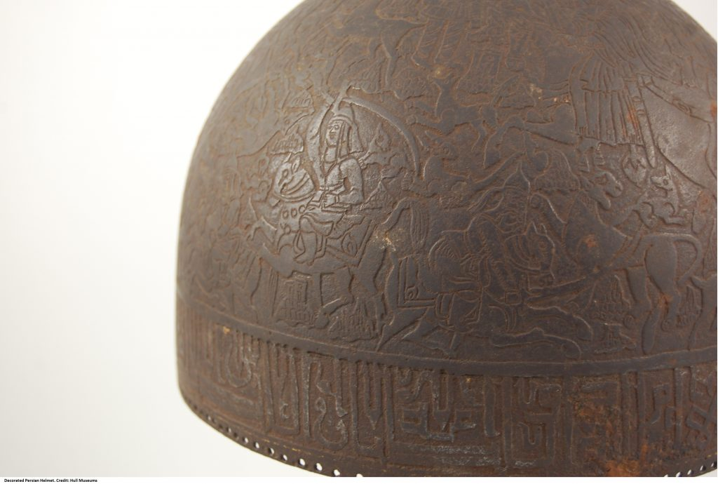 A highly decorative metal helmet. The helmet is decorated with hunting scenes.