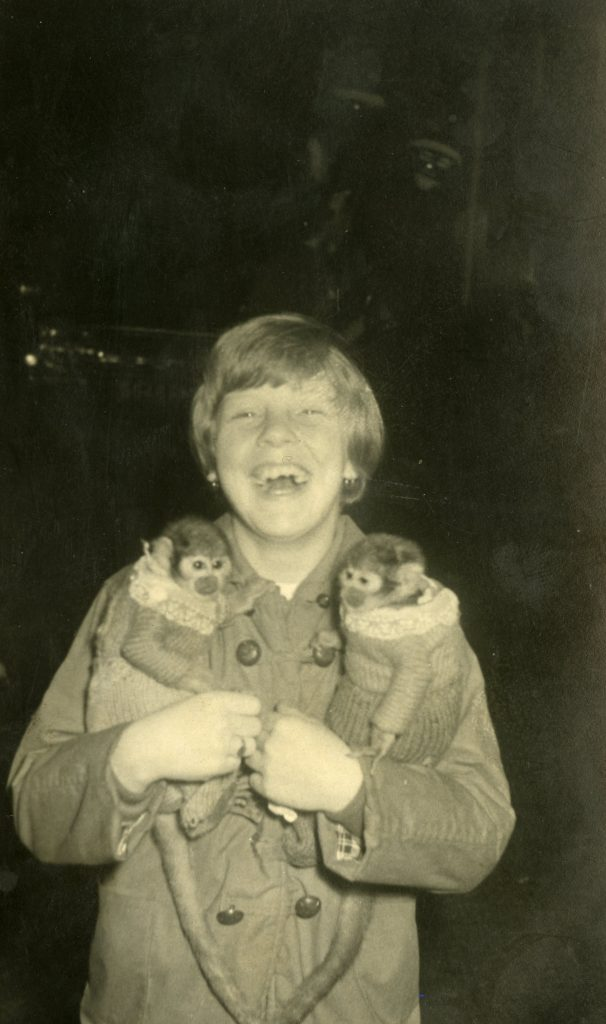 Black and white photograph of a girl holding two monkeys