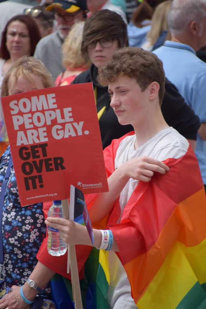 A Pride in Hull attendee, draped in a Pride flag and holding a sign which reads, some people are gay. Get over it.