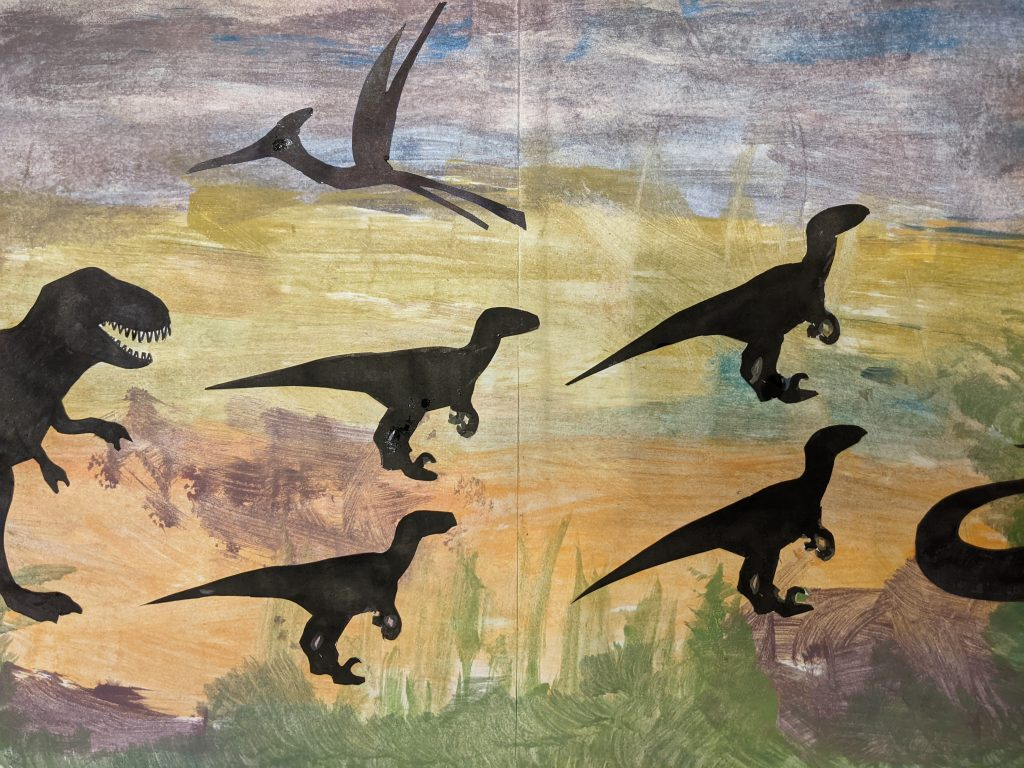 A painting with multiple silhouettes of dinosaurs.