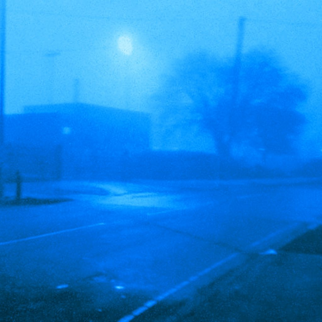 A blue photograph of a road junction, with trees.