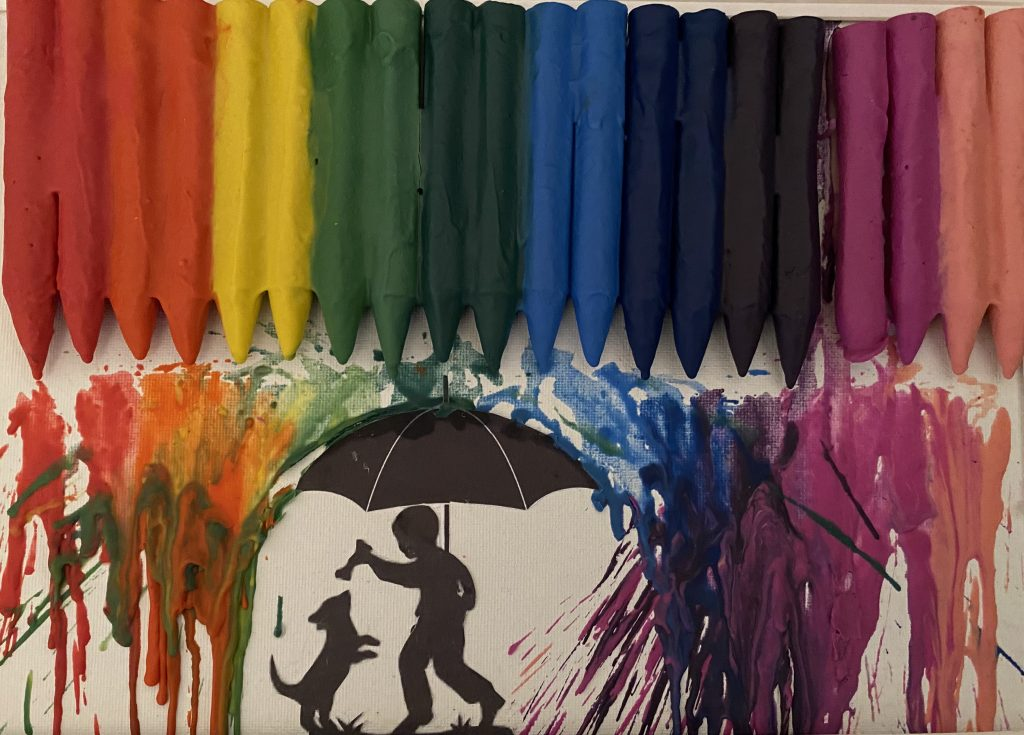 A line of rainbow coloured crayons melting on to a silhouette of a figure with an umbrella and small dog.